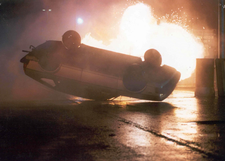 Autostunts met een explosie op de achtergrond.